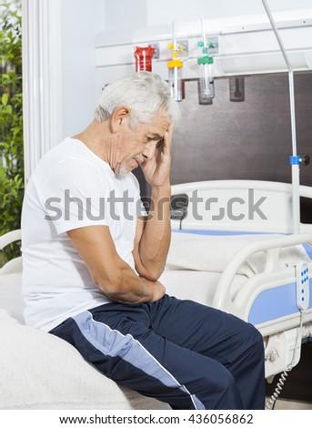 Sad Senior Patient Sitting On Bed At Rehab Center - stock photo