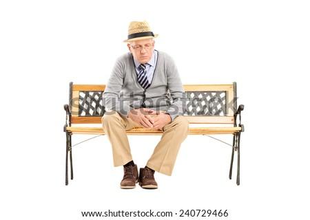 Sad senior thinking seated on a bench isolated on white background - stock photo