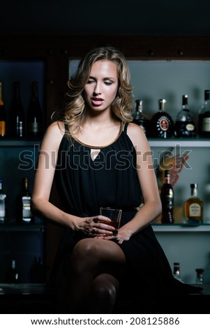 Sad sexy woman sitting on the bar counter at night with glass of whiskey - stock photo