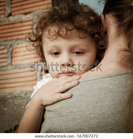 sad son hugging his mother on the background  a brick wall in the day time - stock photo