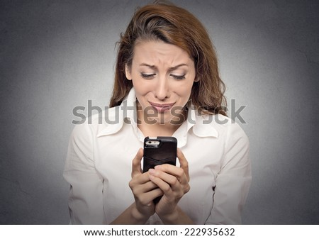 Sad stressed woman looking at her mobile cell phone isolated on grey wall background. Negative human face expressions, emotions, feelings - stock photo