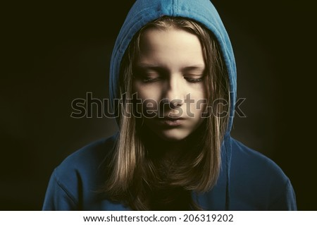 Sad teen girl in hood sitting with closed eyes - stock photo