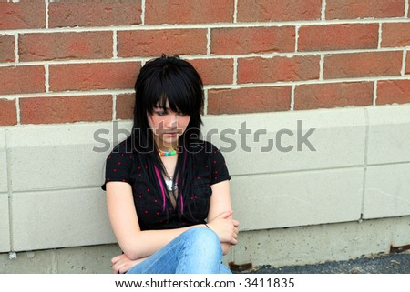 sad teen girl sitting outside of school - stock photo