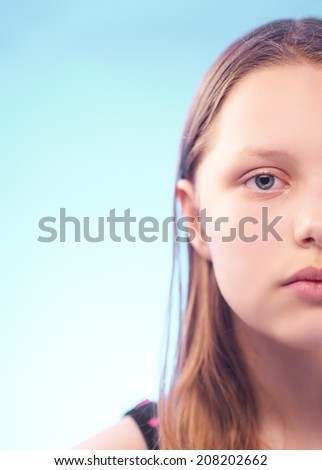Sad teen girl with despair in her eyes. Half of the face - stock photo
