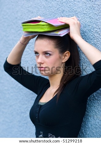 sad teen girl with school books on top of her head - stock photo