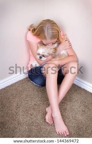 Sad teen in corner holding her shih tzu dog for comfort - stock photo