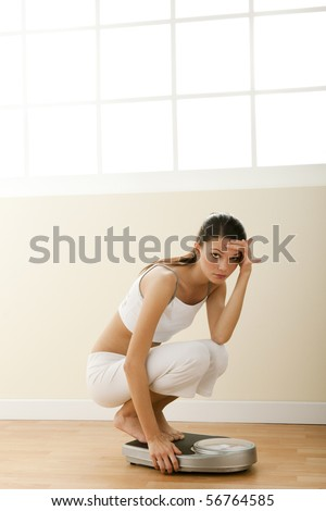 Sad teenage girl on weight scale. Concept: teenage diet problems. - stock photo