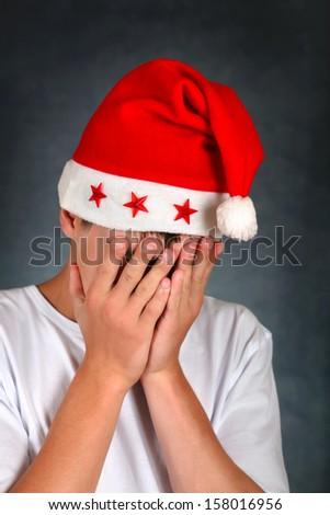 Sad Teenager in Santa's Hat On the Dark Background - stock photo