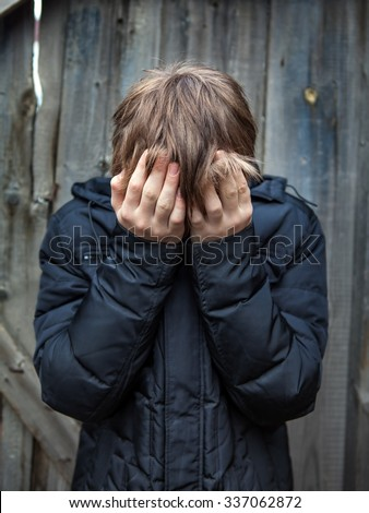 Sad Teenager on the Wooden Wall Background - stock photo