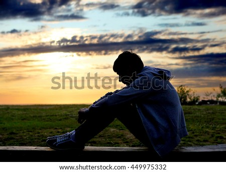Sad Teenager Silhouette at the Sunset Background - stock photo