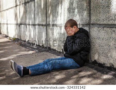 Sad Teenager sit by the Wall on the Street - stock photo
