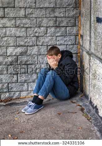 Sad Teenager sit in the Corner on the Street