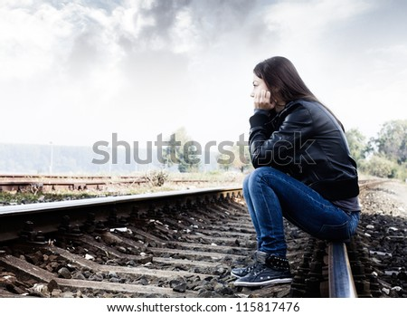 Sad teenager sitting on the tracks, looking into the distance and thinking.