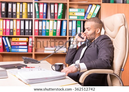 sad thinking man in the office with handset - stock photo