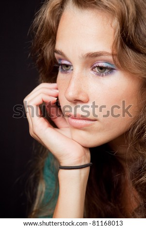 Sad thoughtful pensive woman over dark background - stock photo