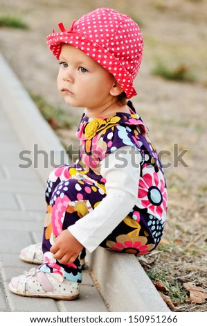 sad toddler girl sitting outdoors - stock photo