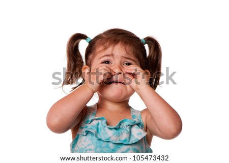 Sad unhappy crying cute little young toddler girl wiping tears, isolated. - stock photo