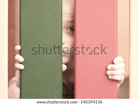 Sad unhappy five years old blond caucasian child girl looking through the fence - stock photo