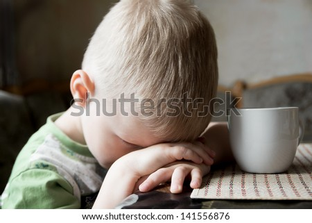 Sad upset tired worried little child (boy) lying on his hands close up portrait - stock photo