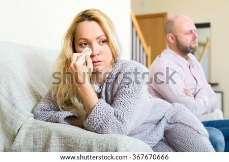 Sad wife wiping her tears with a handkerchief after a conflict in a family. Her stressed husband in sitting in a background - stock photo