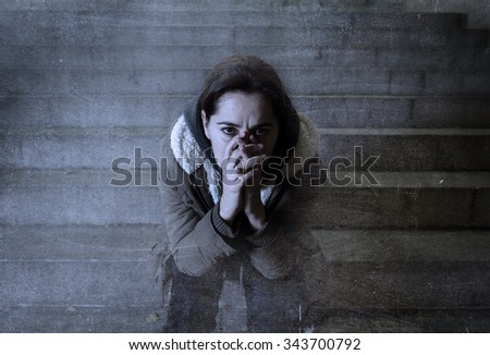 sad woman alone on street subway staircase suffering depression looking sick and helpless sitting lonely as female victim of abuse concept  in  dark urban night grunge background grunge dirty edit - stock photo