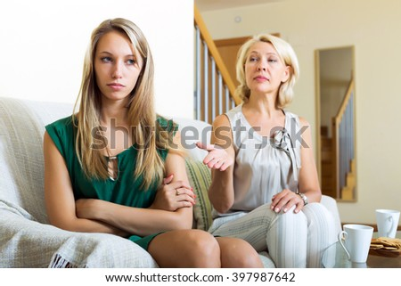 Sad woman and her mature mother having conflict on sofa   - stock photo