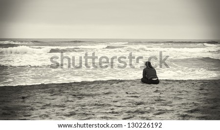 Sad woman at the beach in sepia colors. - stock photo