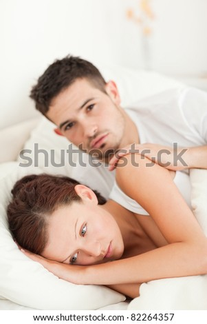 Sad woman comforted by her husband in their bedroom