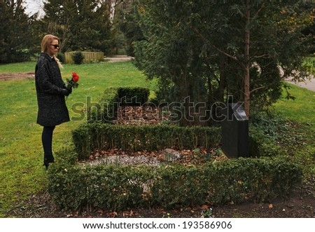 Sad woman grieving in a cemetery holding red roses. Young woman standing at the gravestone of her family member. - stock photo