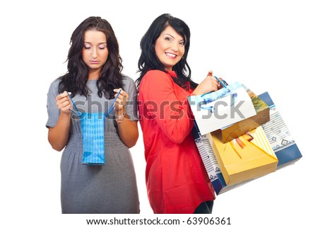 Sad woman holding  and looking in single small bag  and the other women smiling and holding many shopping bags - stock photo
