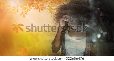 Sad woman holding her forehead with her hand against autumn scene - stock photo