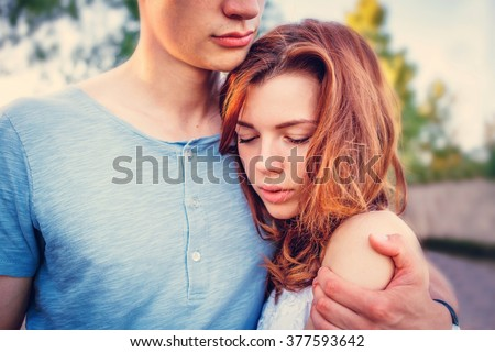 Sad woman hugging her boyfriend and looking down couple problems concept - stock photo