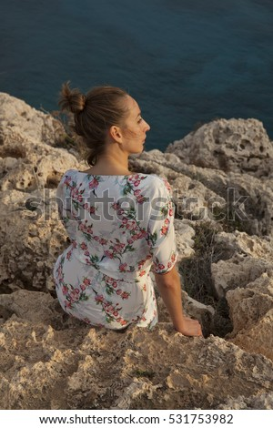 Sad woman in summer dress sitting on the rocks by the sunset