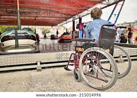 sad woman in wheelchair watching on carousel - stock photo
