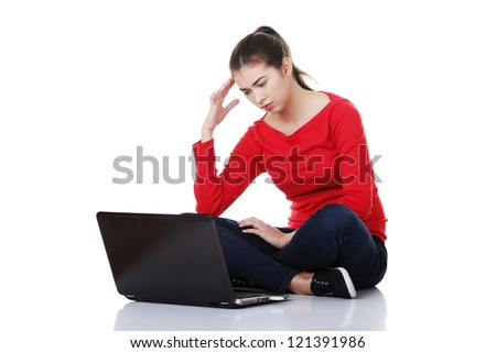 Sad woman looking on laptop screen. Isolated on white. - stock photo