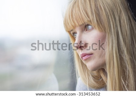 sad woman looking out of window - stock photo