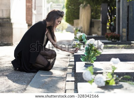 Sad woman on her knees in front of a grave