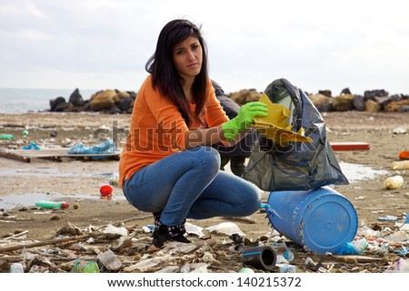 Sad woman picking up dump on dirty beach - stock photo