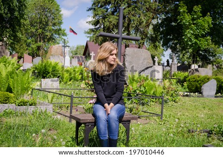 Sad woman sit near lover grave in cemetery. Patriot soldier died. National Lithuania flag.  - stock photo