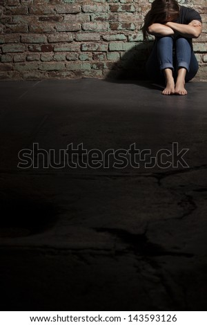 Sad woman sitting alone against brick wall with copyspace. - stock photo
