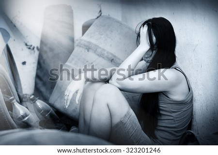 Sad woman sitting and thinking about her problems. - stock photo