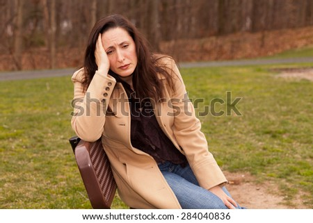 Sad woman sitting on a bench on a cloudy day with a coat looking lonely - stock photo