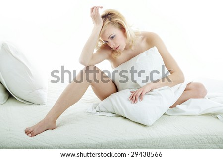 Sad woman sitting on the bed at the morning - stock photo
