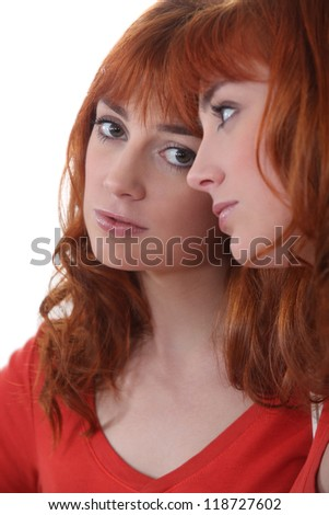 Sad woman staring at her reflection in the mirror - stock photo