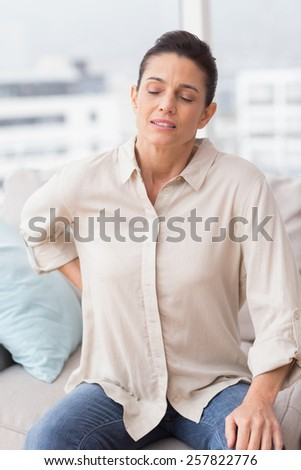 Sad woman suffering from backache while sitting on sofa