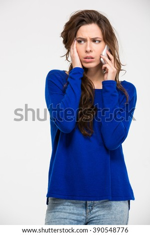 Sad woman talking on the phone isolated on a white background - stock photo