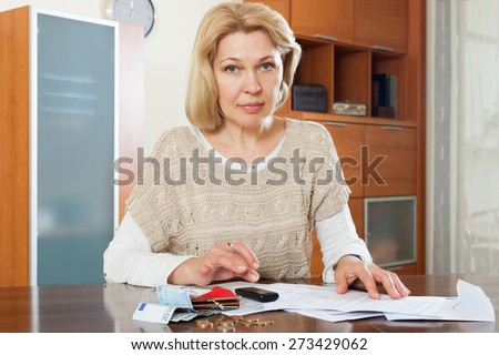 Sad woman thinking about the financial issue at  home - stock photo
