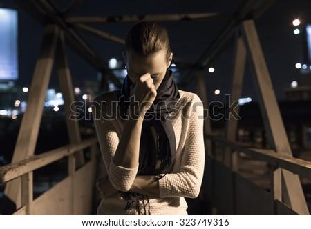Sad woman walking in the city at night.  - stock photo