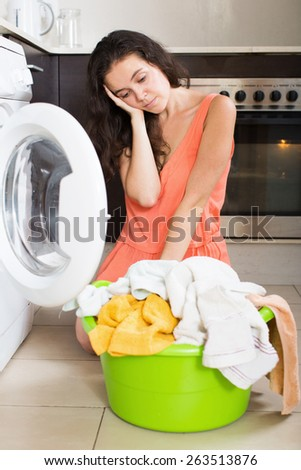 Sad woman washing clothes in machine at home - stock photo