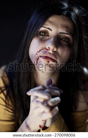 Sad woman with bruises and blood asking for help - stock photo